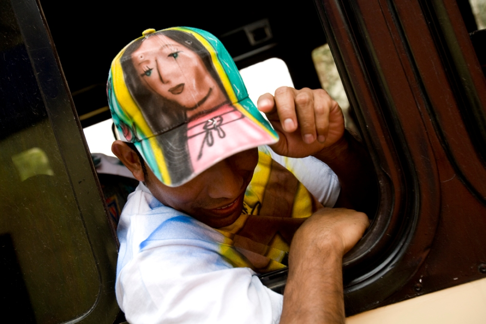 A pilgrim from Chalma, outsdie of Mexico City, shows off his hat, with an airbrushed Virgin of Guadalupe on it on his way home.