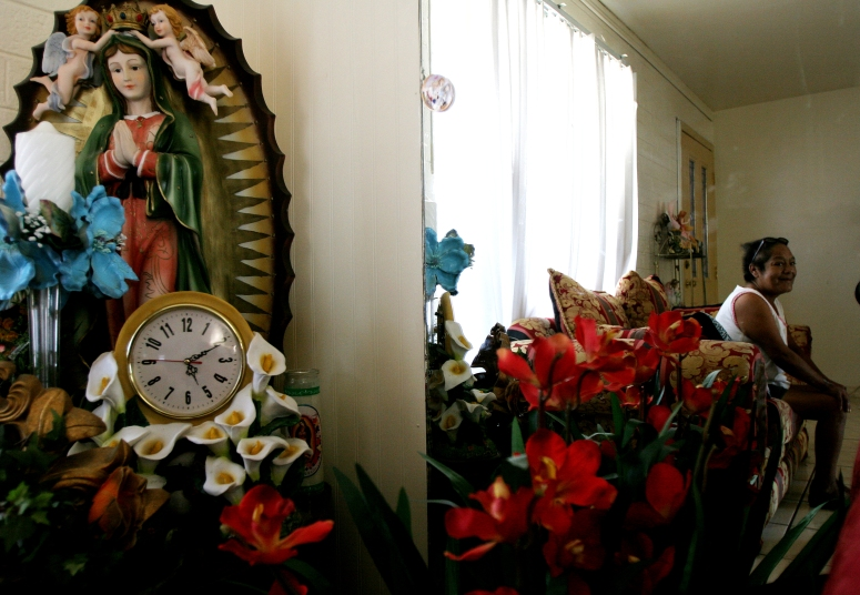 A diabetic patient is seen in the mirror next to her decorated Virgen of Guadalupe before leaving for dialysis in Phoenix, Ariz.