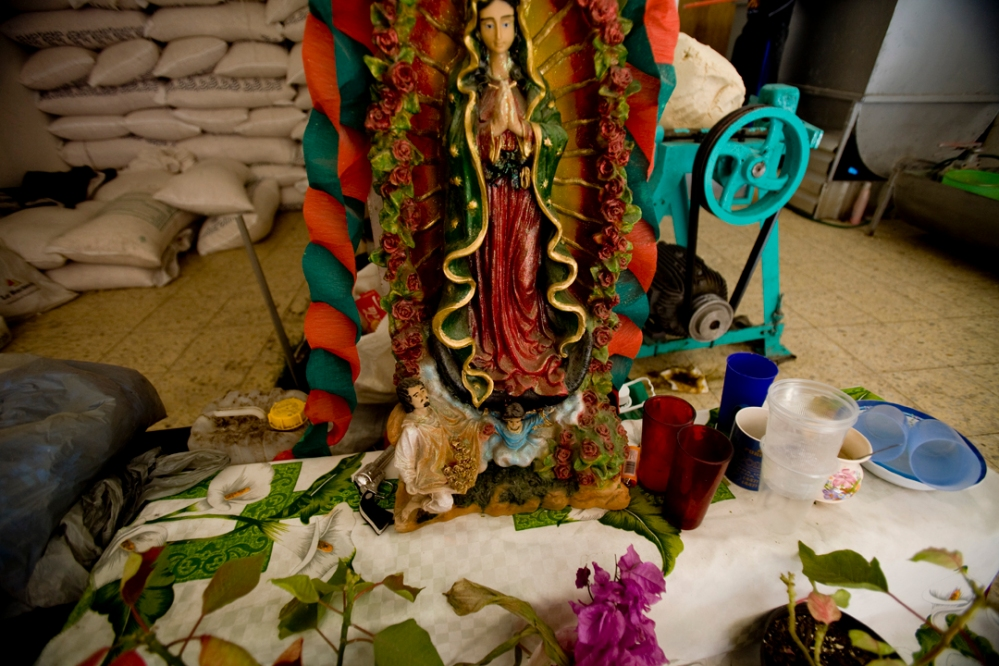 A Virgen de Guadalupe in a bakery in Morelia, Mexico has money and a small toy gun at her feet.