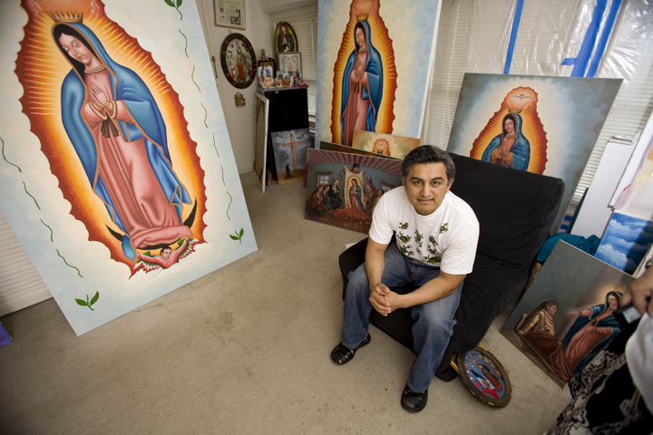 Vladimir Cuevas, a San Fransisco artist sits in his studio with over fifteen paintings of her image. Those pictured with him will be placed in a church built for the Virgen de Guadalupe in Manila, Philippines