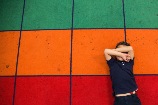 Phoenix - April 21, 2016 - ASU Now - A student rests on the classroom carpet in Rachel Wade's kindergarten class at Balsz Elementary School in Phoenix Thursday afternoon on April 21st, 2016. The student teachers are part of a new program where they visited students at their home. Photo by Deanna Dent/ASU Now